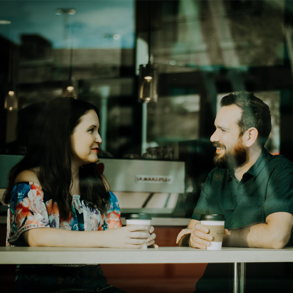 a woman and man talking over coffee