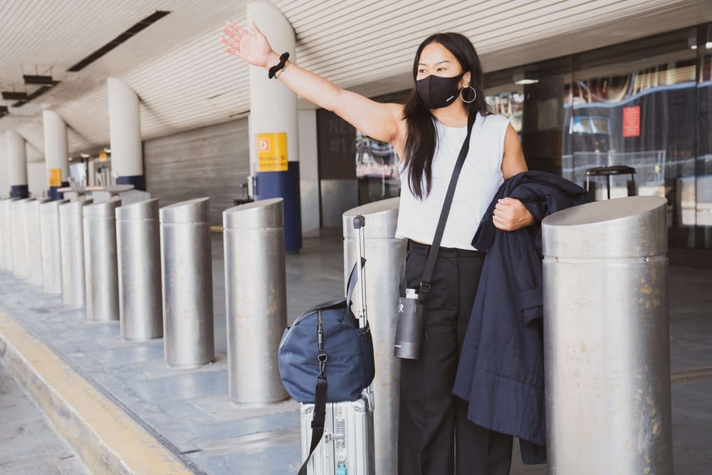 woman wearing a mask hailing for a cab at the airport