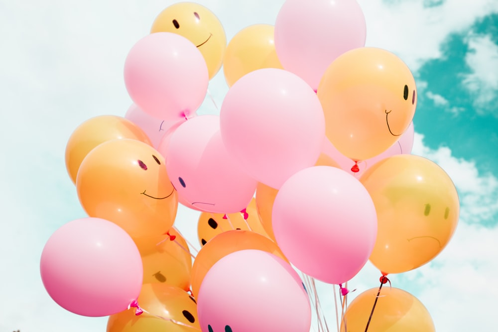 pink and orange balloons with faces on them