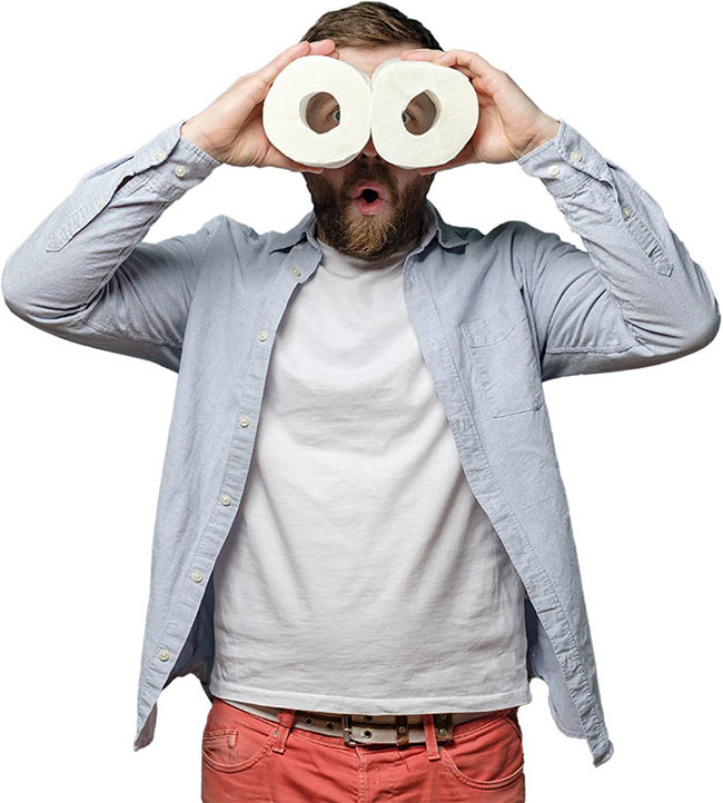 A man holding toilet roll to his face as binoculars.
