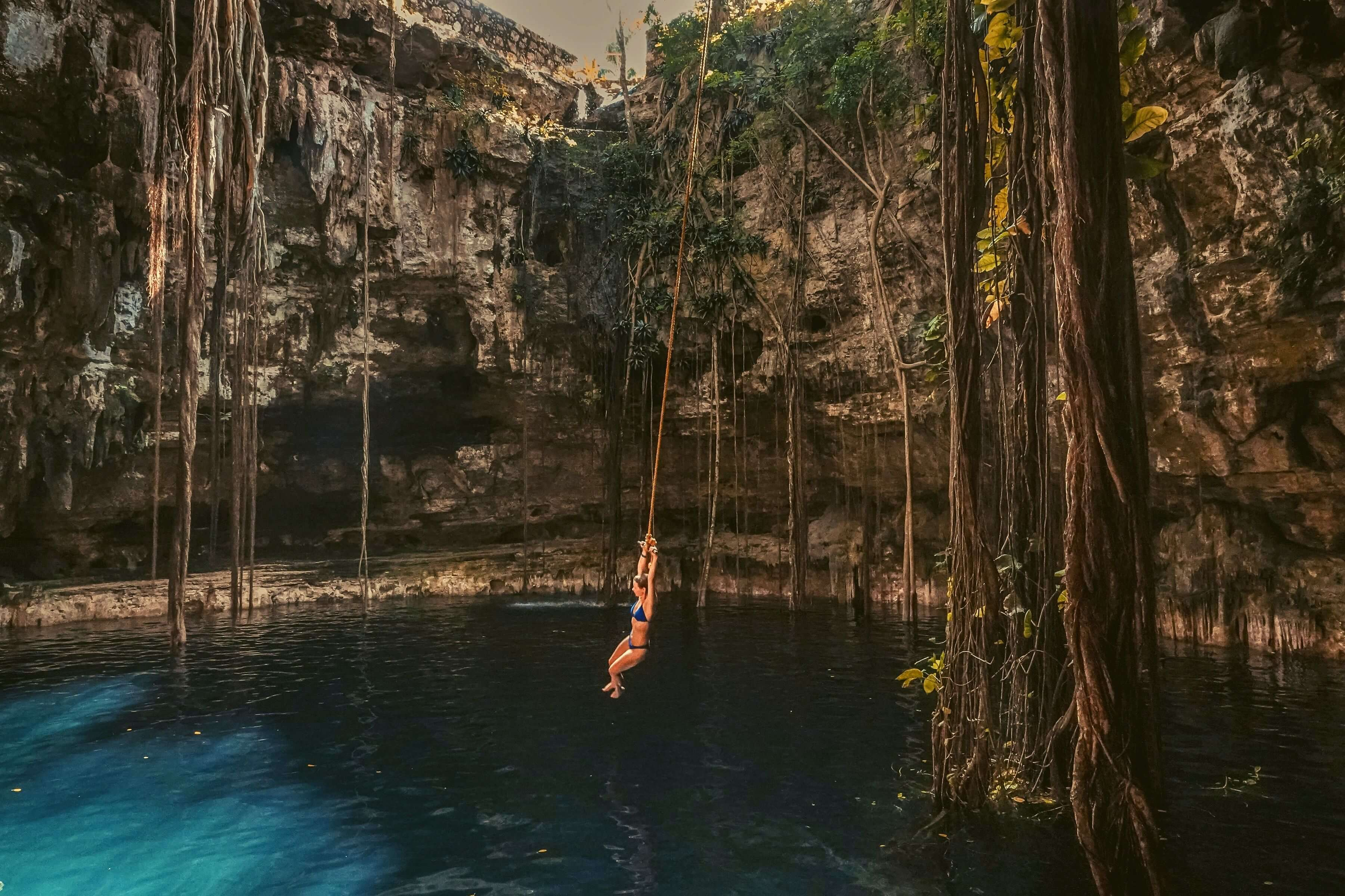 Woman swinging above a natural pool