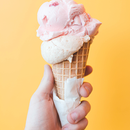 A hand holding a waffle cone with two scoops against a yellow background.