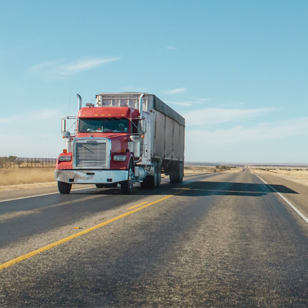 An 18 wheeler with a red cab drives down the interstate in a desert against a clear blue sky.