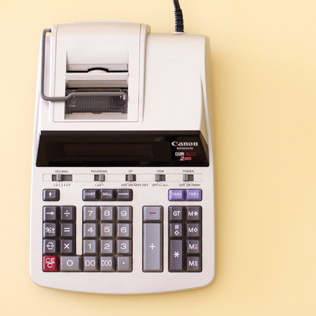 A manual printing calculator sits on a pale yellow background.
