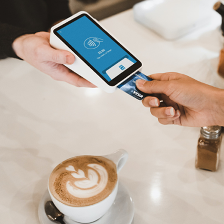 A zoomed in scene of a customer paying for a coffee with their card via a phone scanner device.