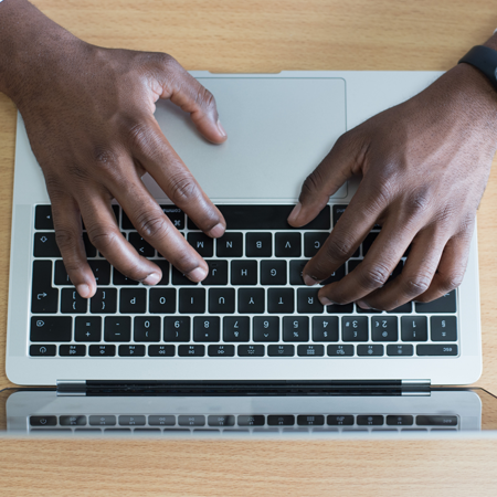 A pair of male hands type on a laptop keyboard.