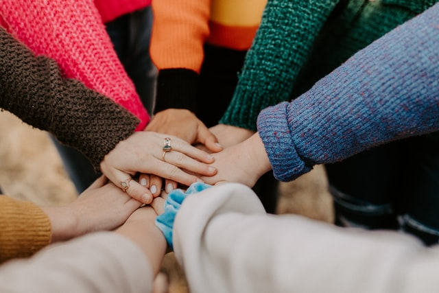 A group of individuals' hands meet, stacked together in a display of teamwork