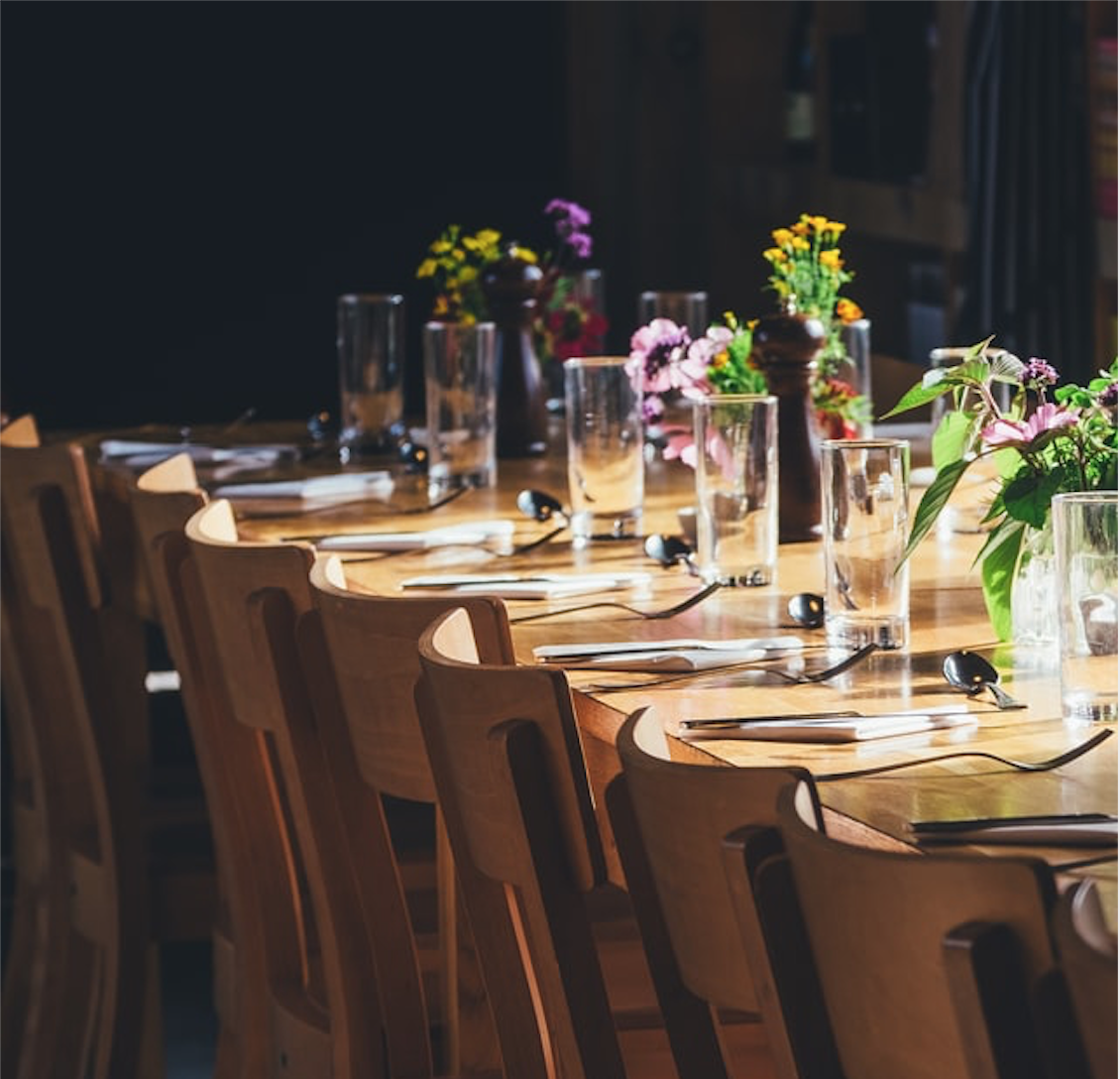 A low-lit table setting awaits guests, with colorful floral arragements and crystal glasses.