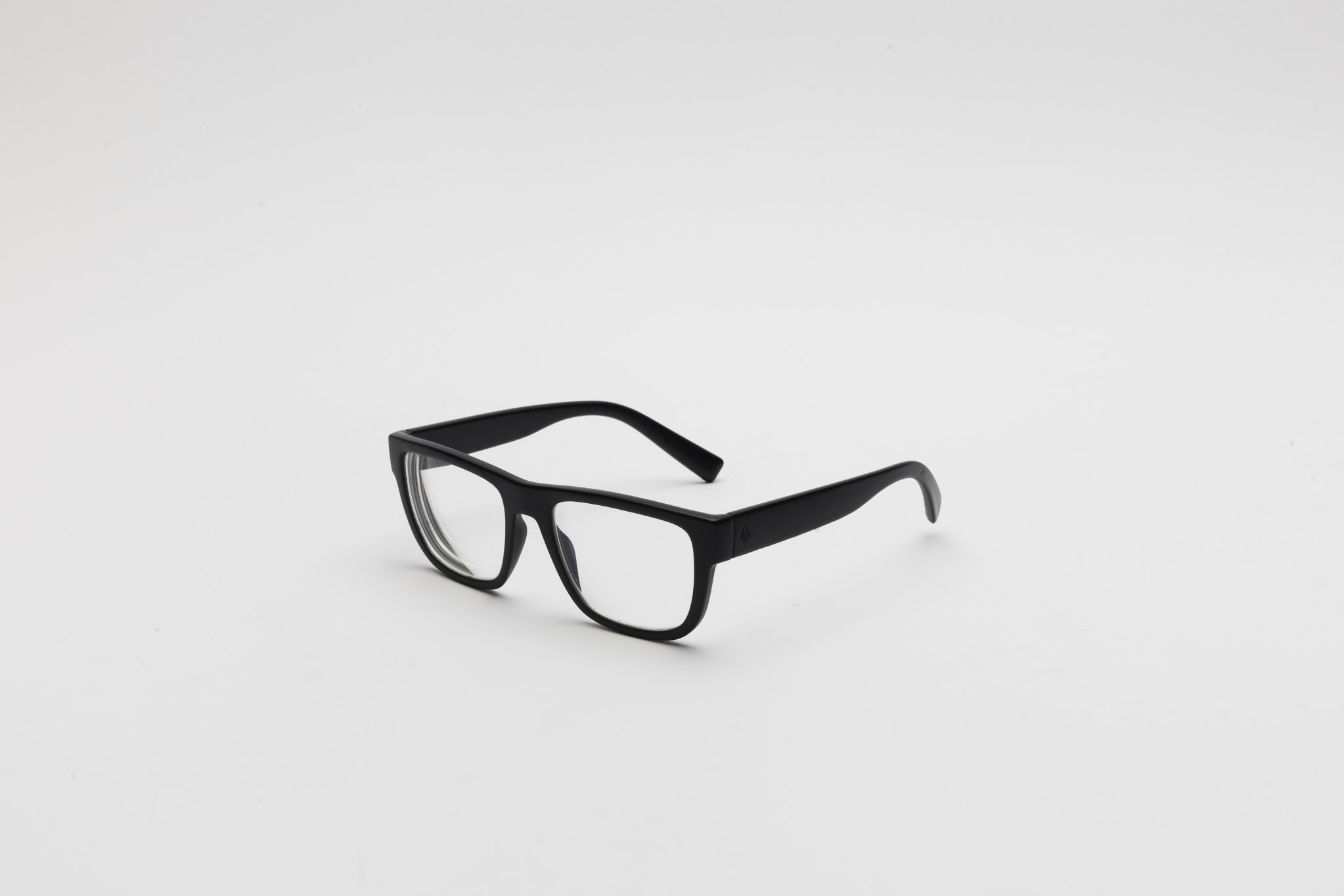 A pair of black eyeglasses that are placed in a white background.