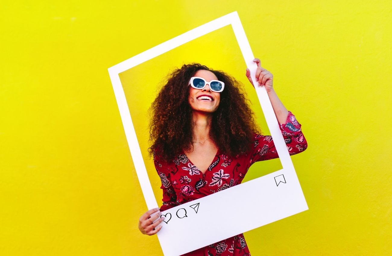 A woman holds up a piece of poster board cut into a frame with her face in the center. She is smiling and wearing sunglasses.