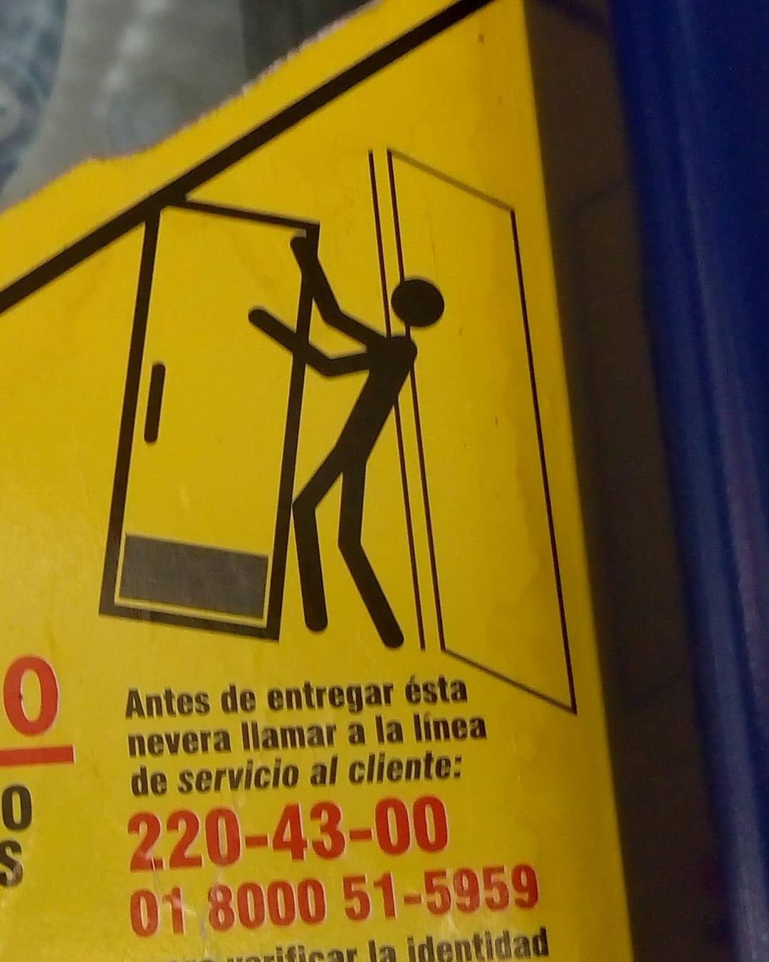Ícono de advertencia de persona cargando un refrigerador. Parece que este último estuviera abalanceándose contra la persona.