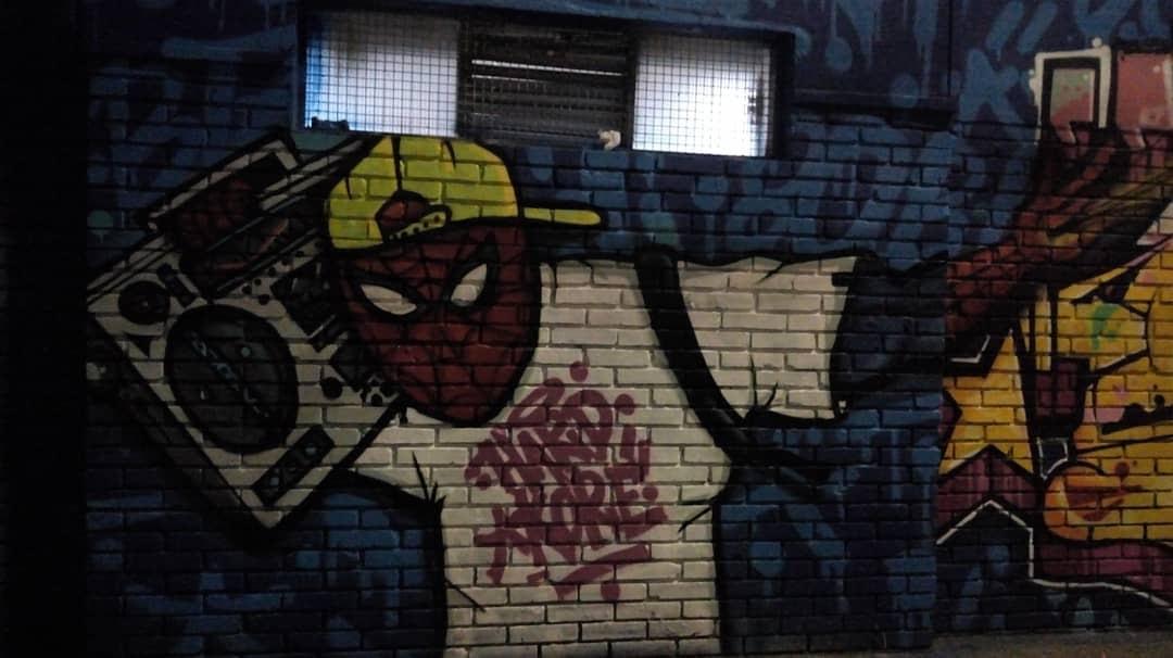 Mural en pared de ladrillo con dibujo de Spider-Man, vistiendo una gorra y con una grabadora en el brazo.