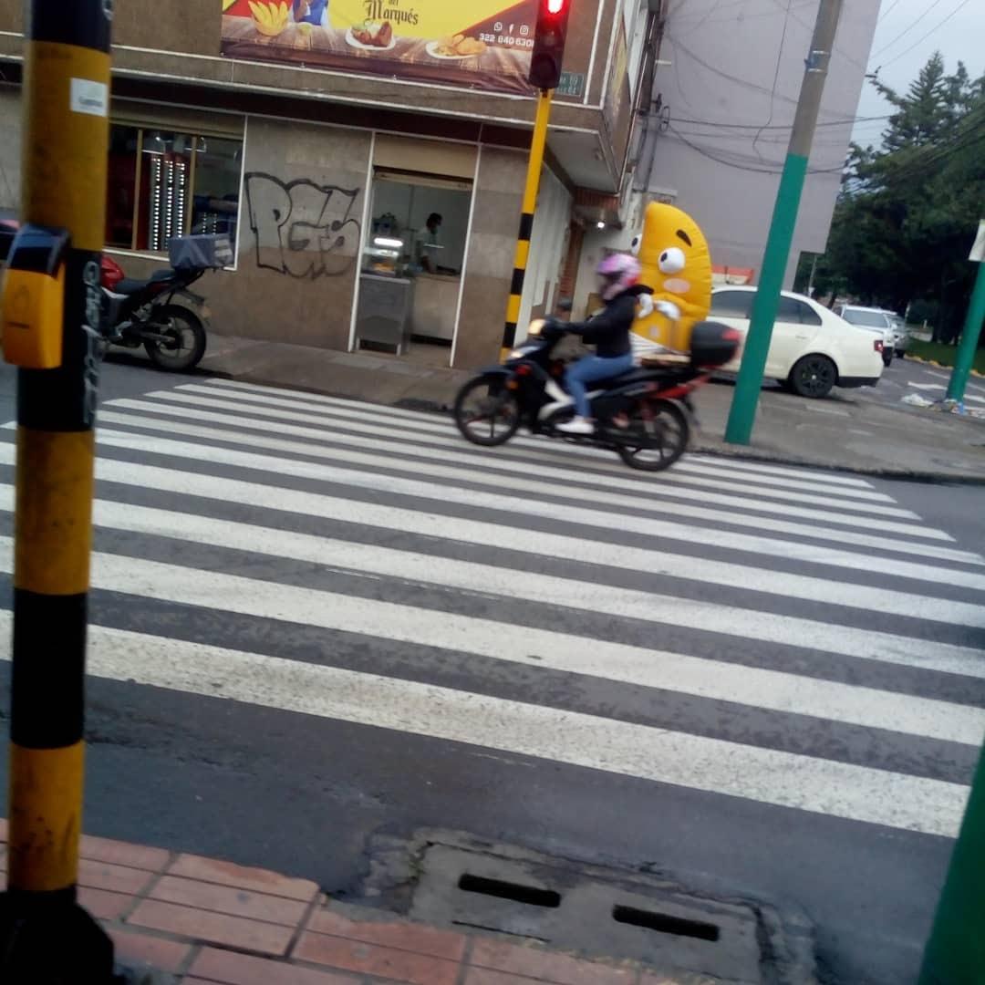 Al otro extremo de la calle una motociclista pasa al pie de una persona con disfraz de empanada.