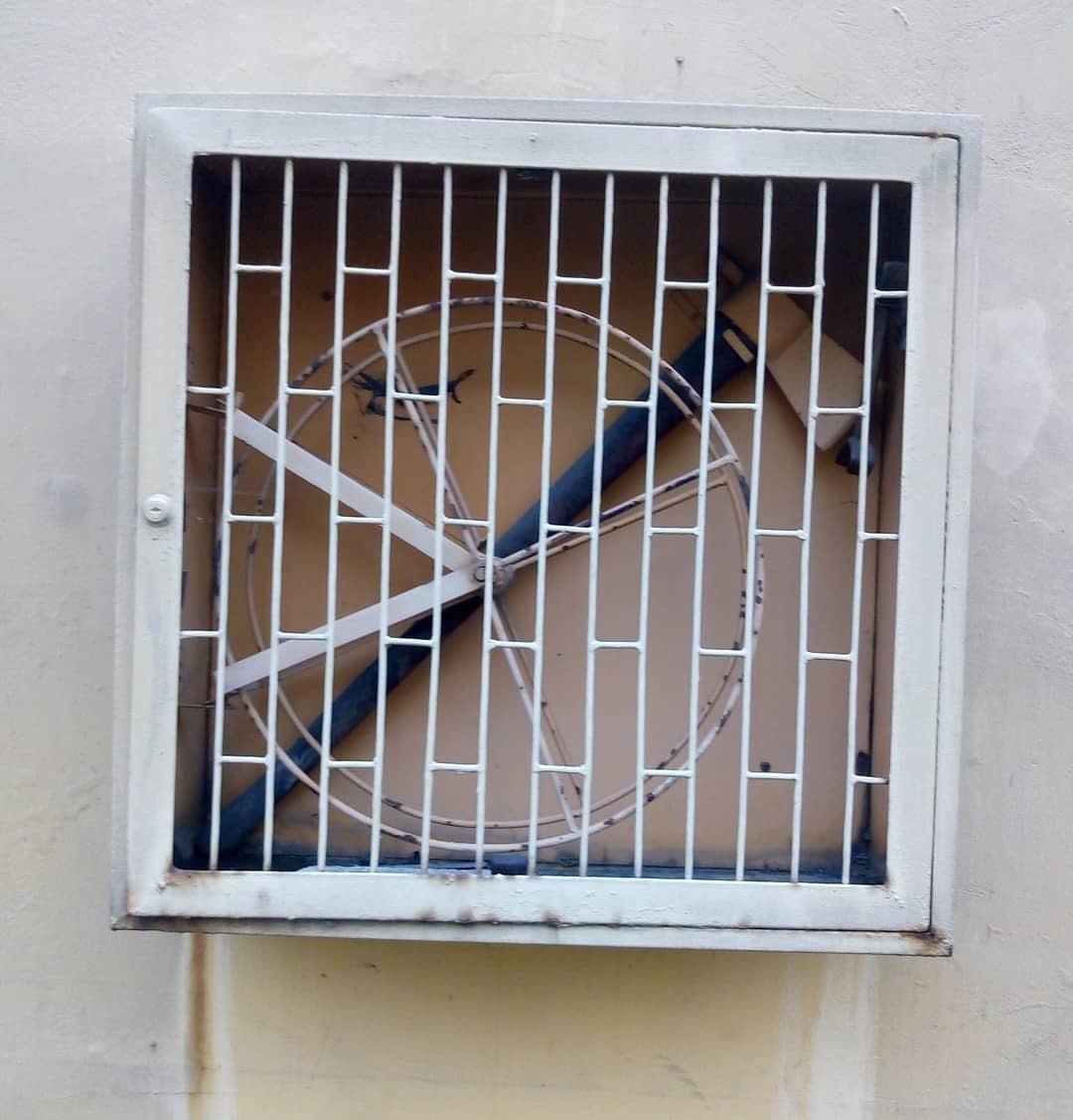 Caja de metal en una pared que tiene una rueda y un hacha en el fondo.