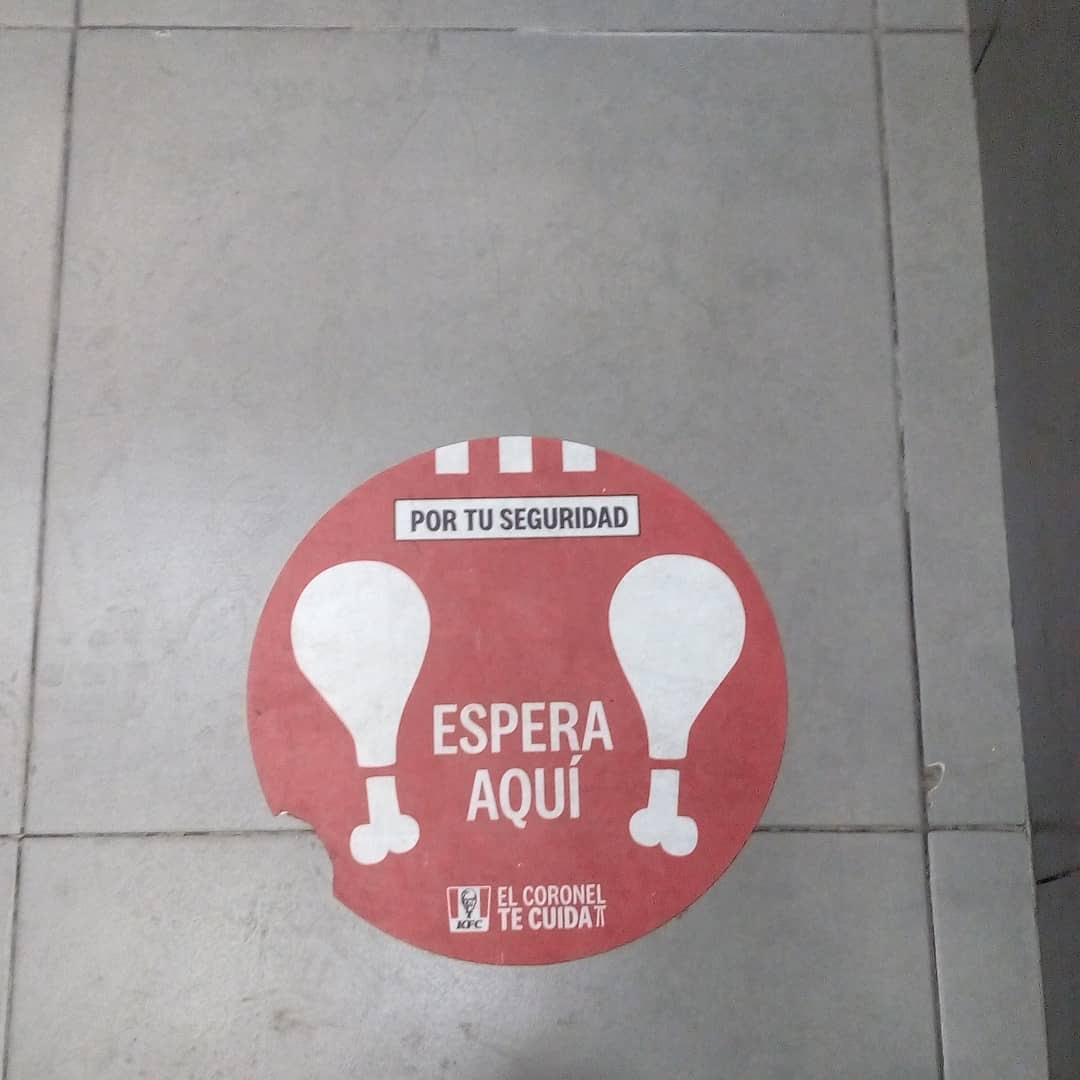 Pegatina o sticker del suelo que dice: Espera aquí. En un emblema de restaurante dice: El coronel te cuida.