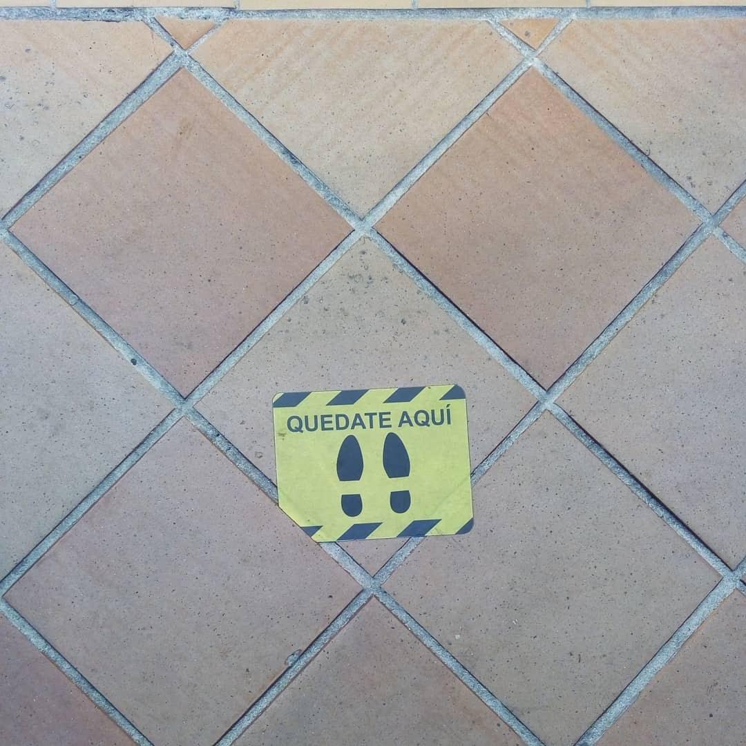 Pegatina o sticker del suelo que tiene huellas y dice: Quédate aquí