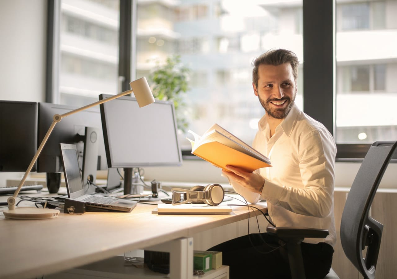 Man sitting on desk holding documents