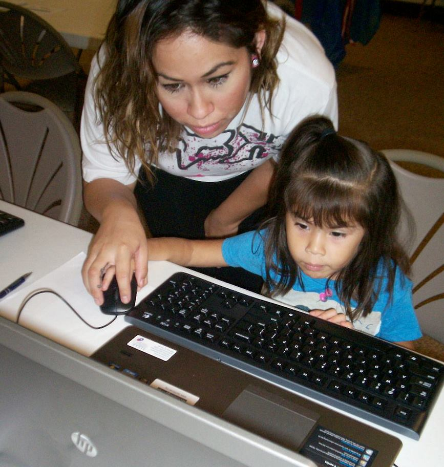 A lady helping a little girl on a TFA laptop.