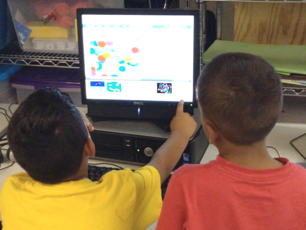 Two kids sharing a computer.