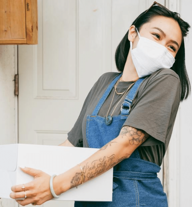 Woman working with mask after pre-work employee screening