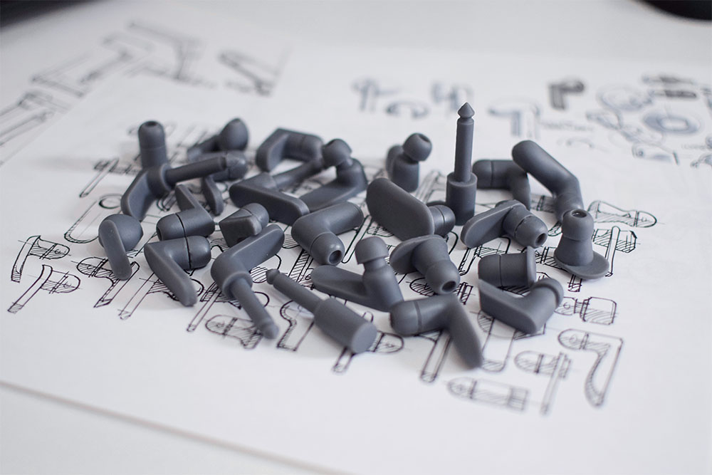 26 3D printed prototypes of the jack plug product laying on top of a page of sketches