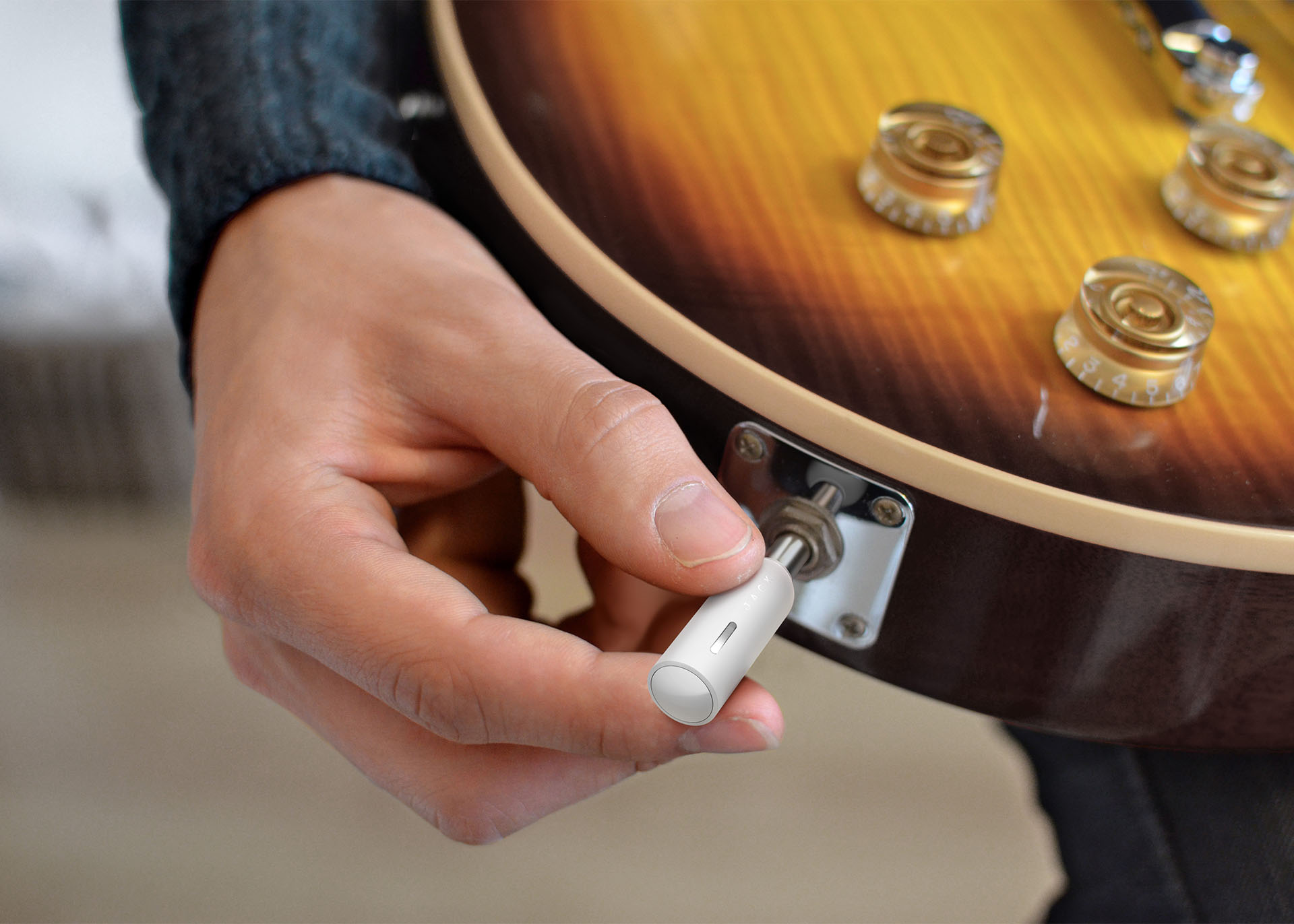 A hand plugging the Jack plug transmitter into the socket of a guitar