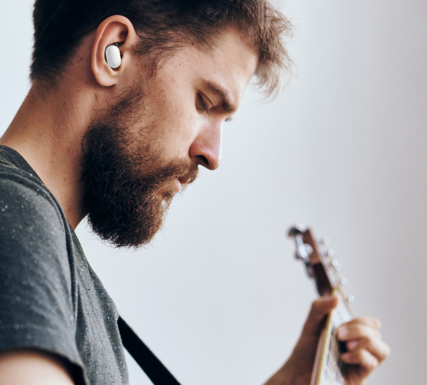 A man playing guitar with the Jack wireless earbuds in his ears