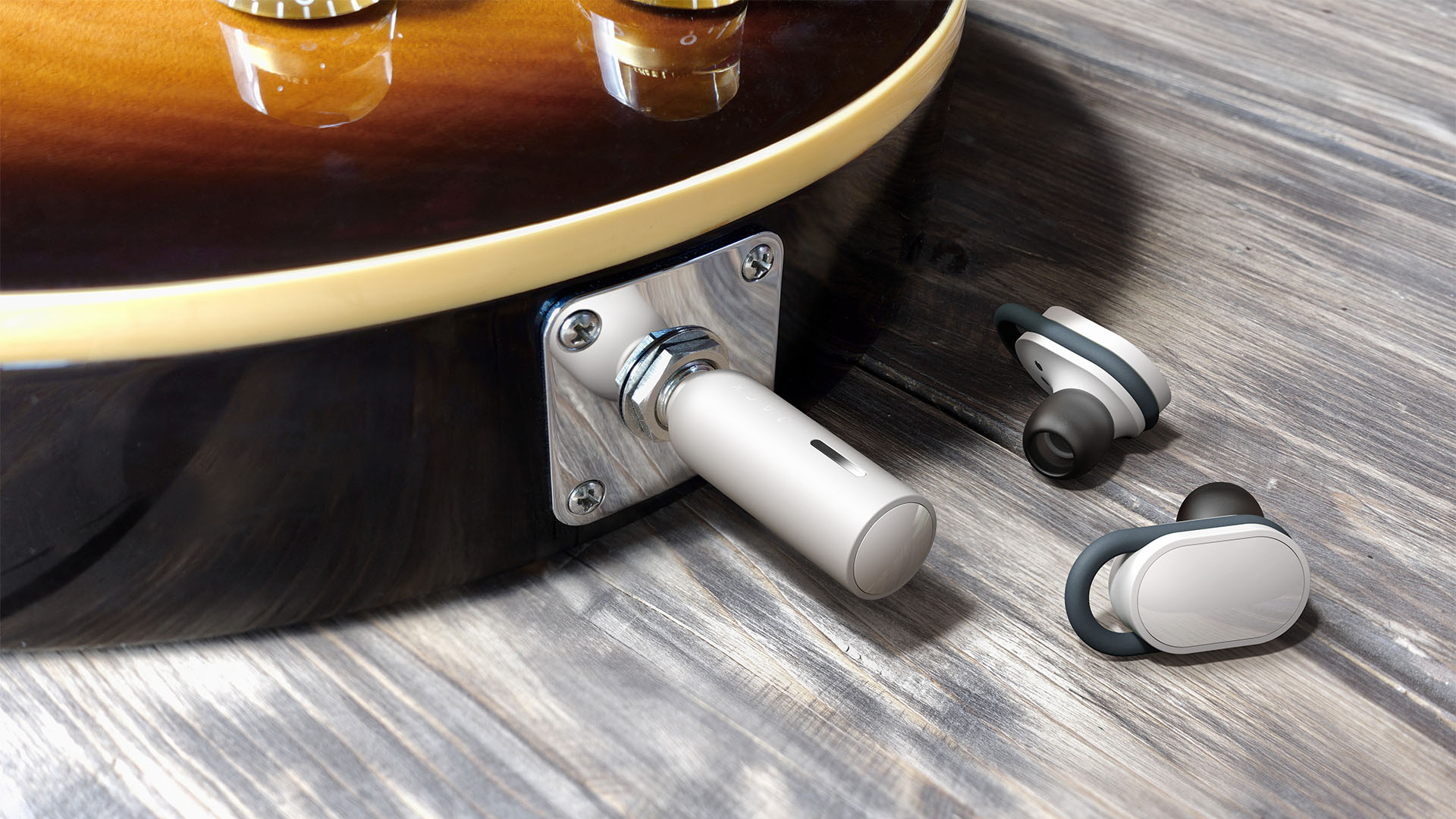Close-up of a guitar with the jack plug transmitter plugged in and earbuds lying next to it