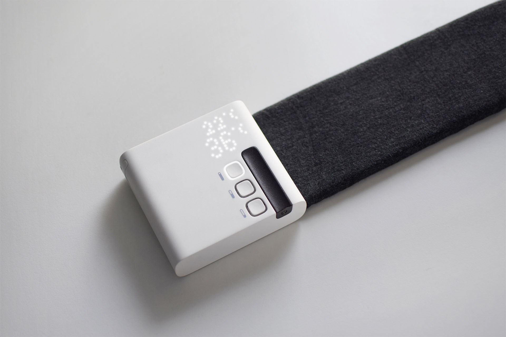 Hero shot of the Stratum heating and cooling desk mat, a minimal white box attached to a narrow fabric mat