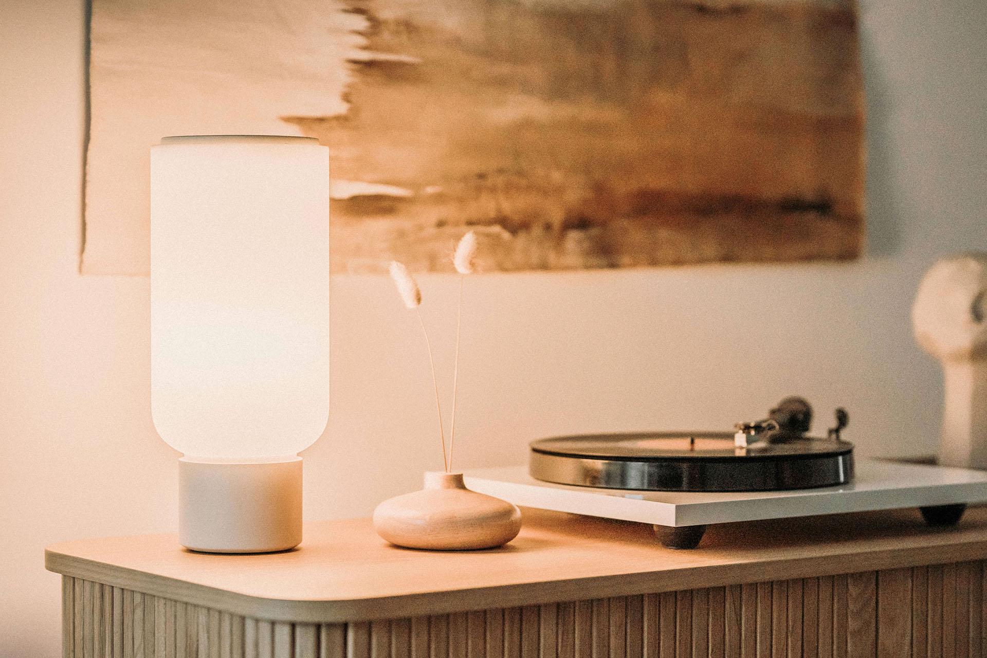 Arpeggio Table Light for Gantri, illuminated and sitting on a minimal sideboard