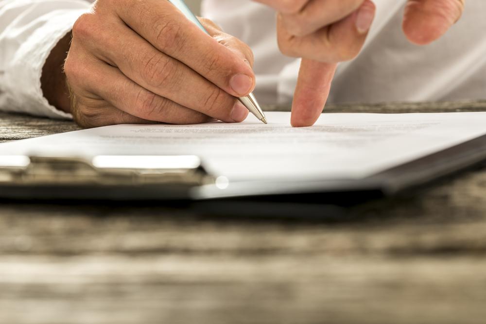 Un employé signe un contrat d'assurances collectives.