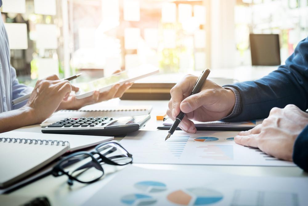 Un conseiller financier explique à son client, à l'aide de documents, les meilleures stratégies d'optimisation fiscale pour son entreprise.