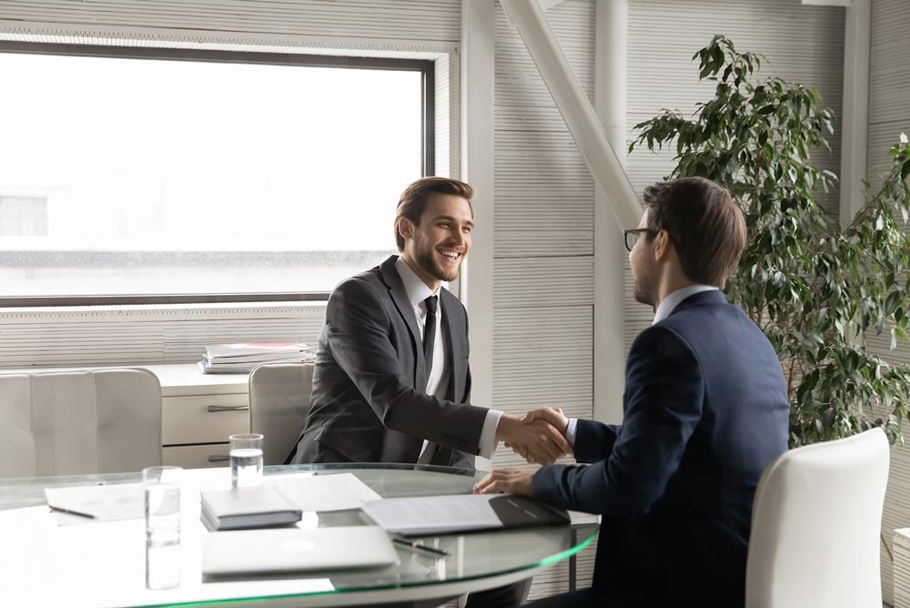 Un propriétaire de PME serre la main de son conseiller financier.