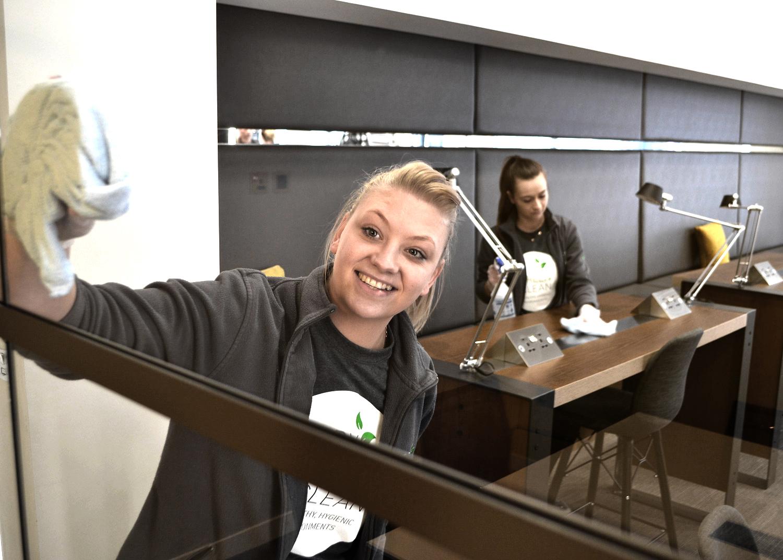Tidy Green Clean staff member cleaning window in office
