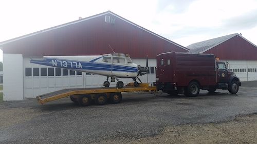 Goliath towing a trailer with a plane on it.
