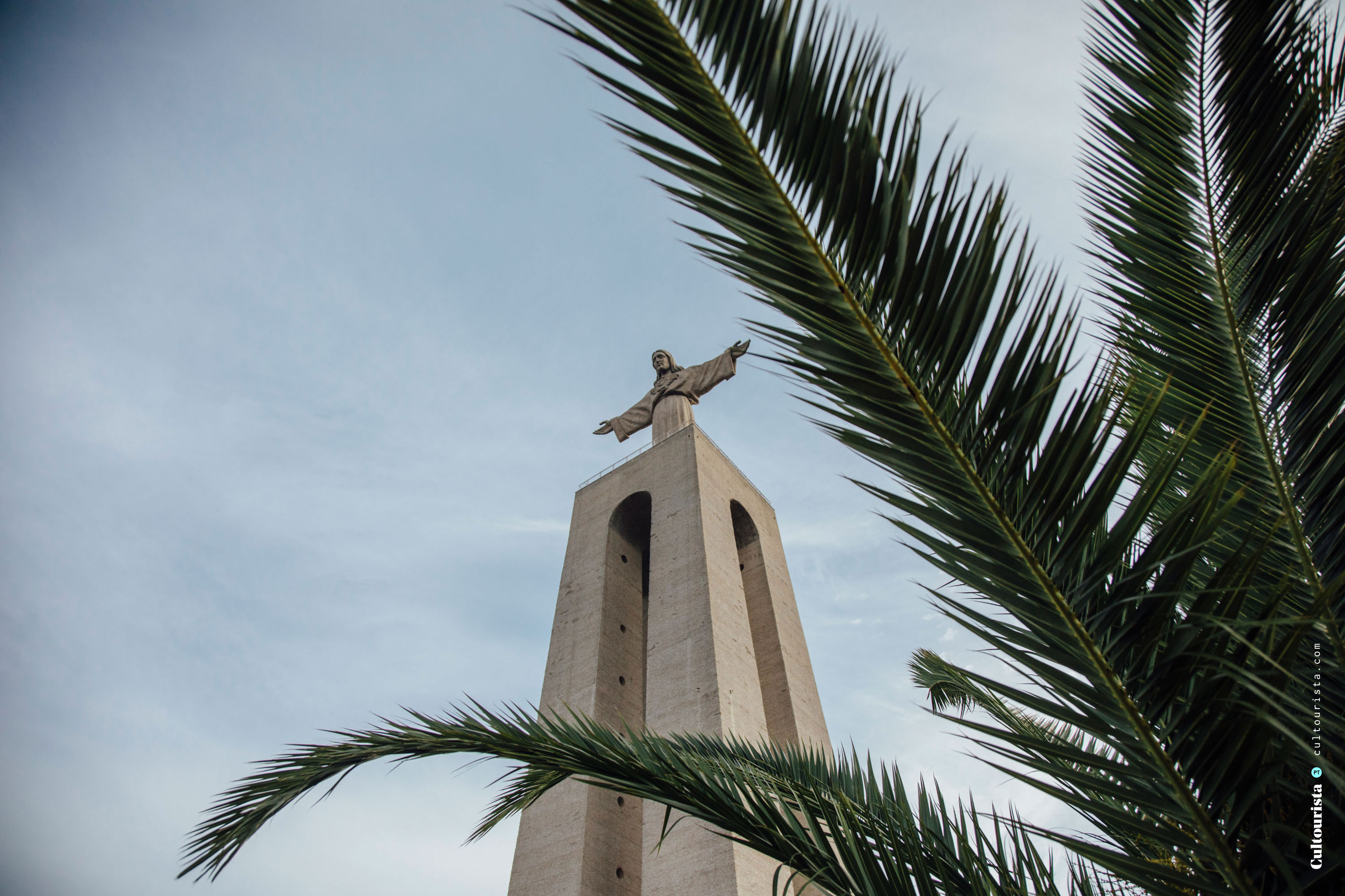 Cristo Rei from the park palm tree in Almada Lisbon Portugal
