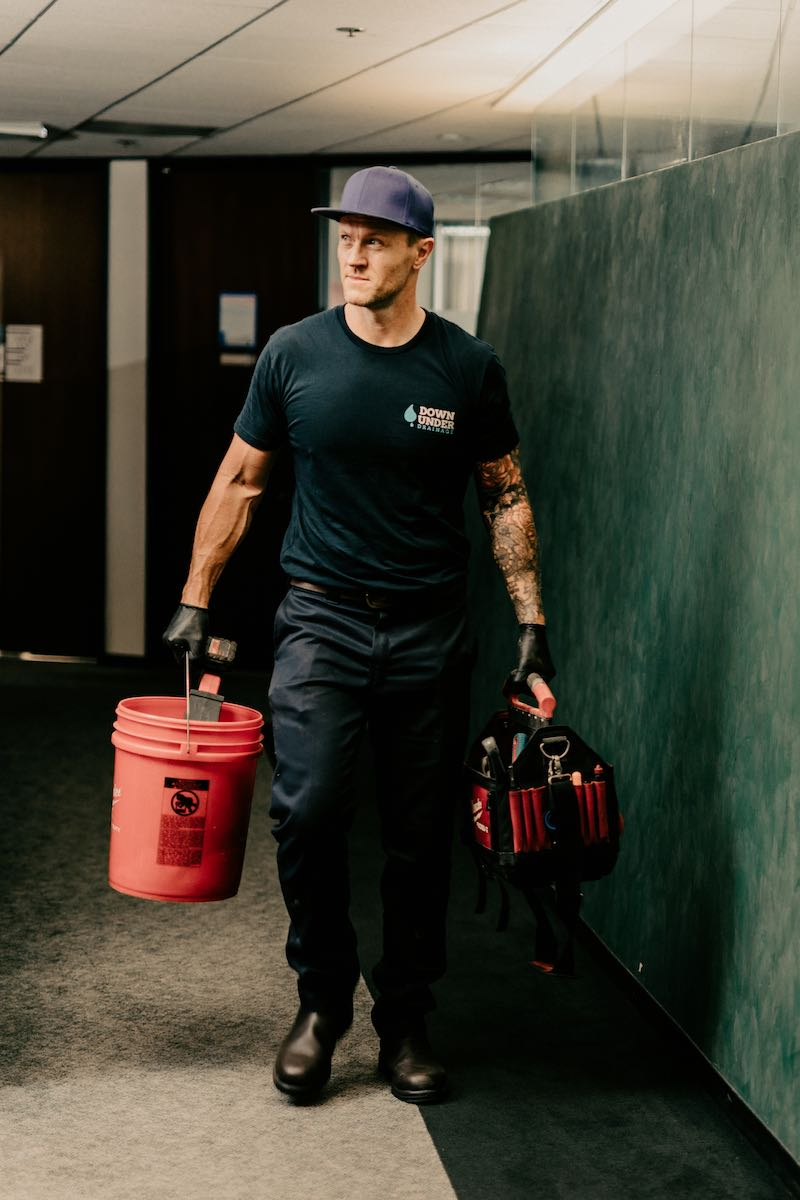 Adam carrying plumbing tools in a building in L.A.