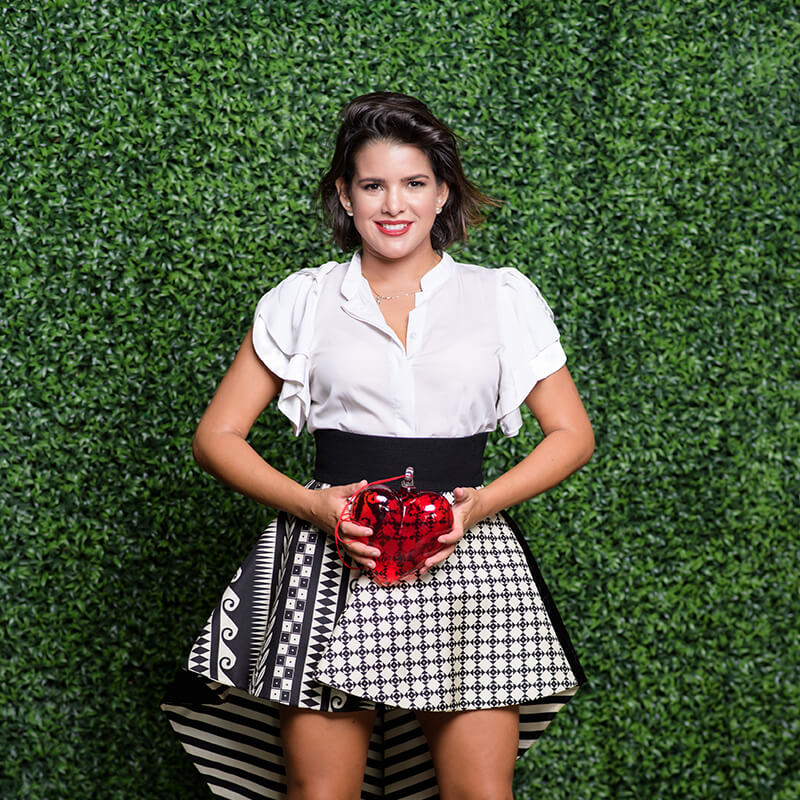 Arianna, Plan Design managing partner, holds a heart figure as she poses in front of a wall of green leaves.