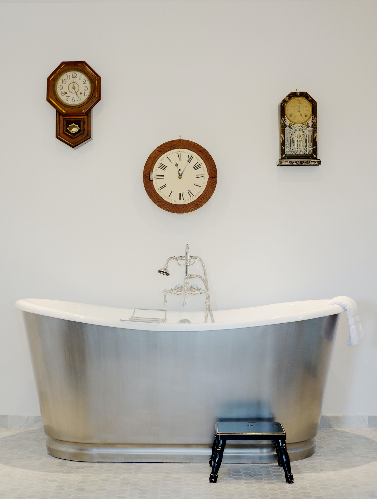 Bathtub with three clocks on wall behind it