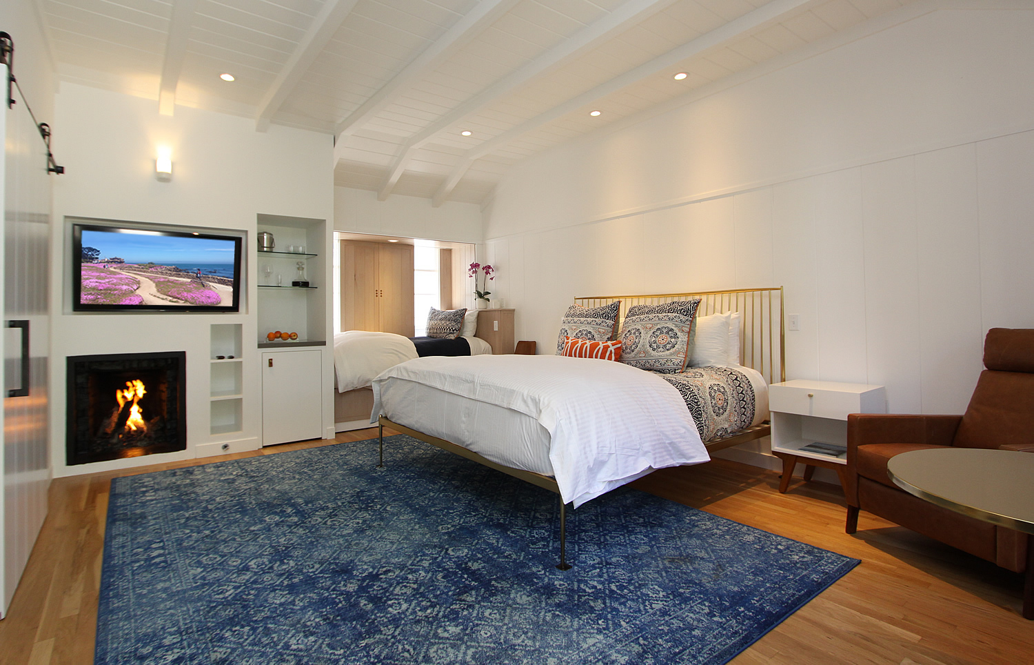 Room with blue carpet, large bed, and TV