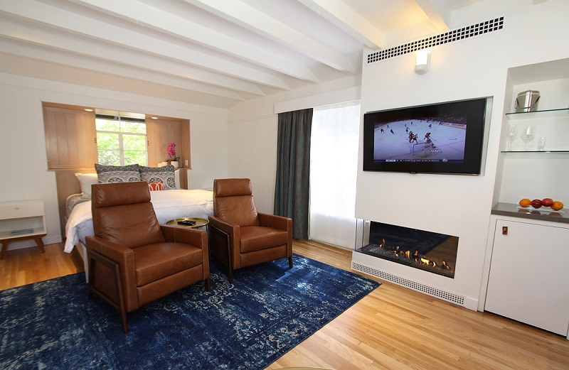 Room with blue carpet, chairs, and TV