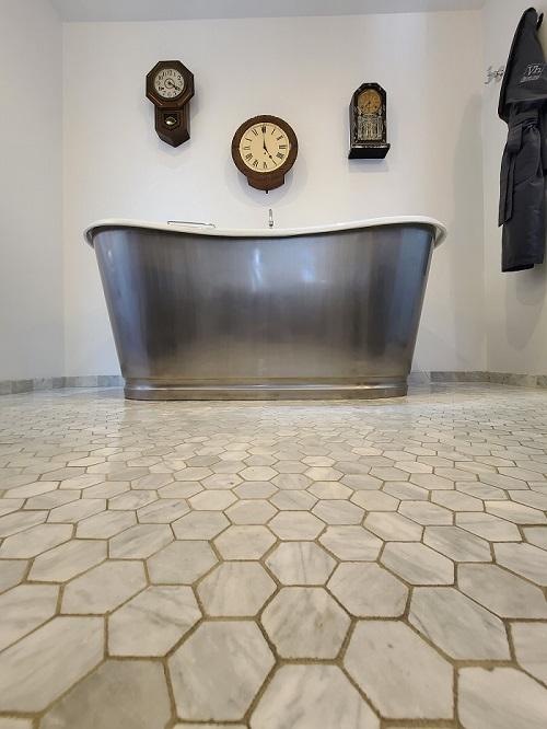 bathtub with three clocks on wall behind it