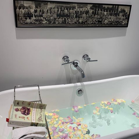 bathtub filled with pedals and a stand with a reading book on it
