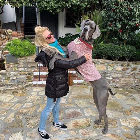 a woman giving a large dog a hug