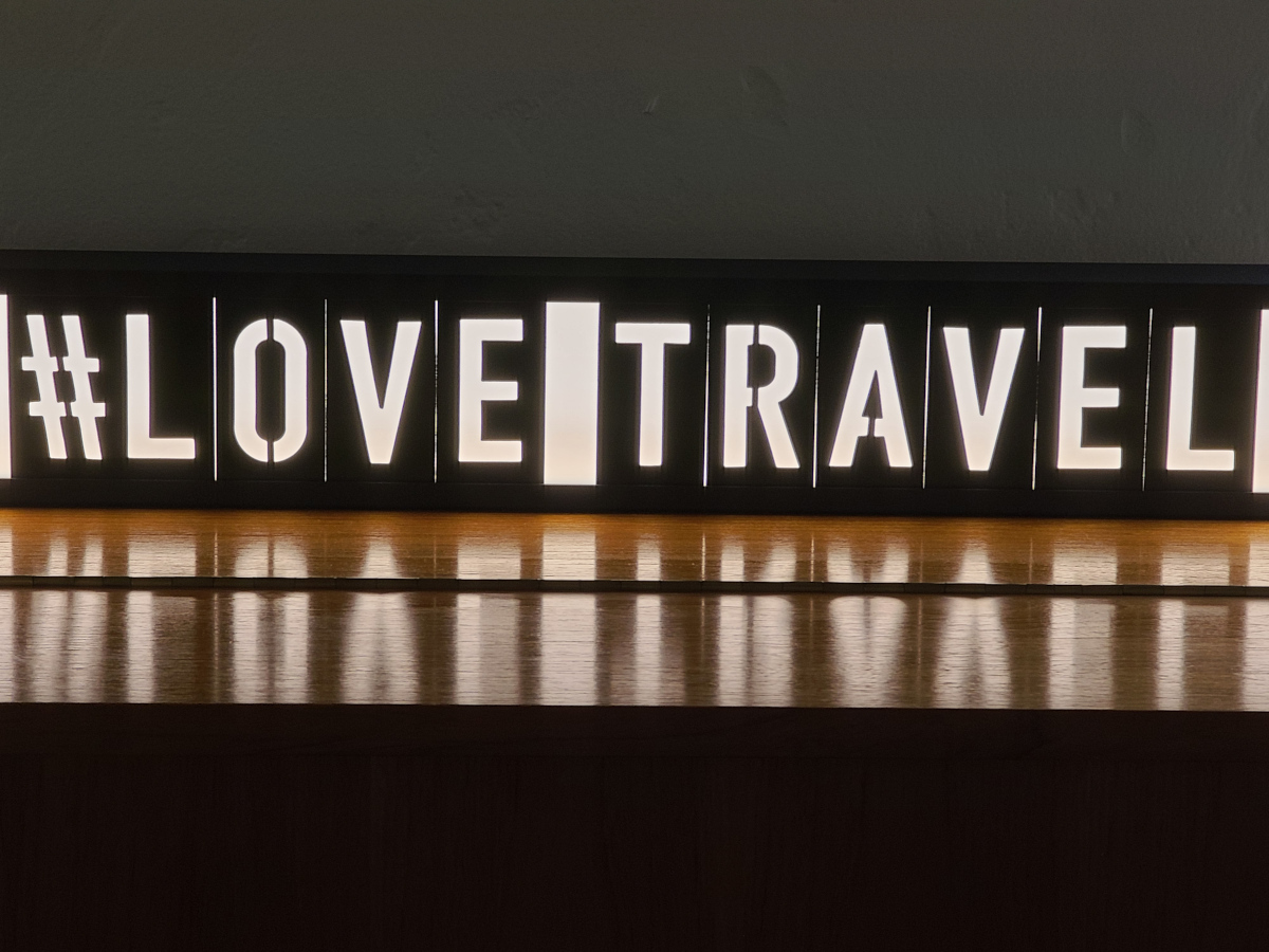 A light sign that says #LoveTravel