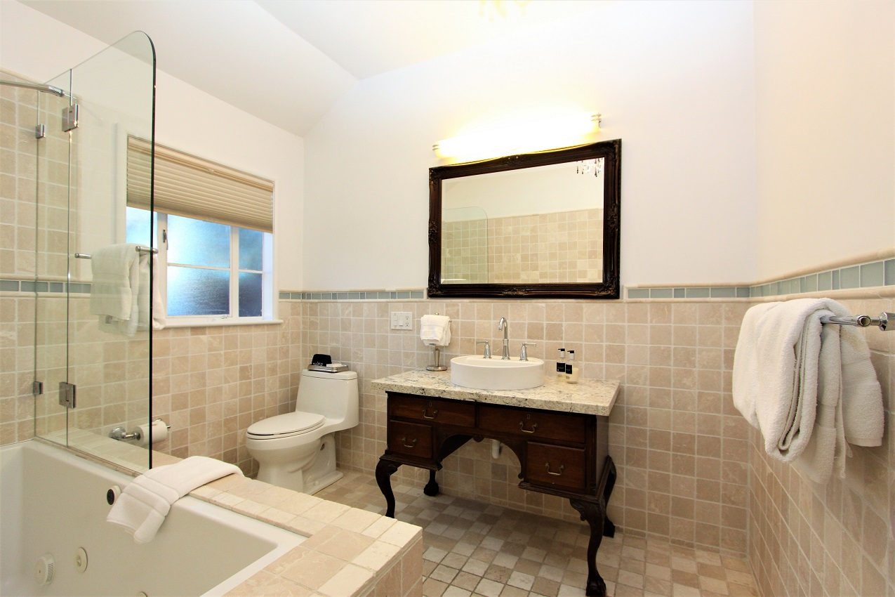 bathroom with tub, mirror, toilet and sink