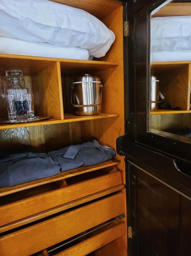 Dresser with pillows, shirts.