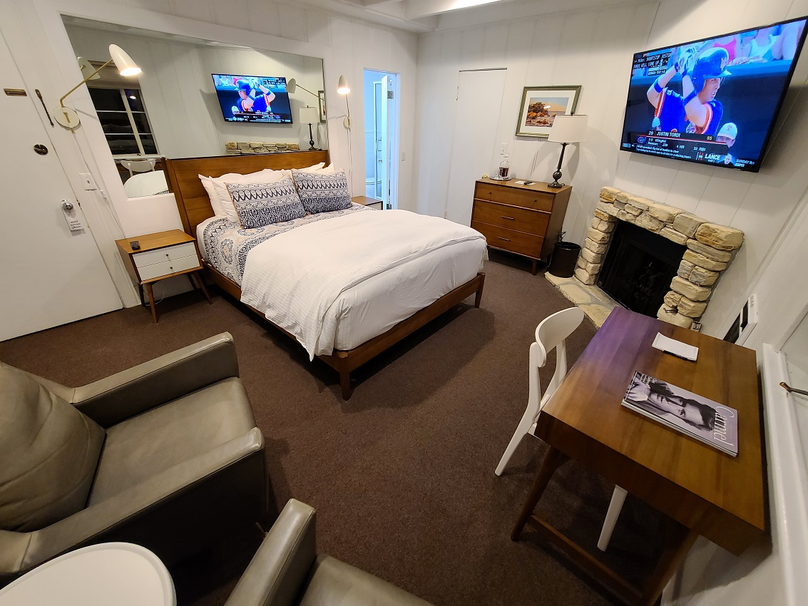 room with bed, TV, fireplace, dresser