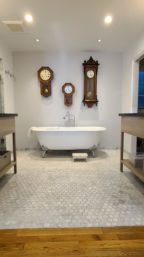 freestanding tub with three clocks on wall over it