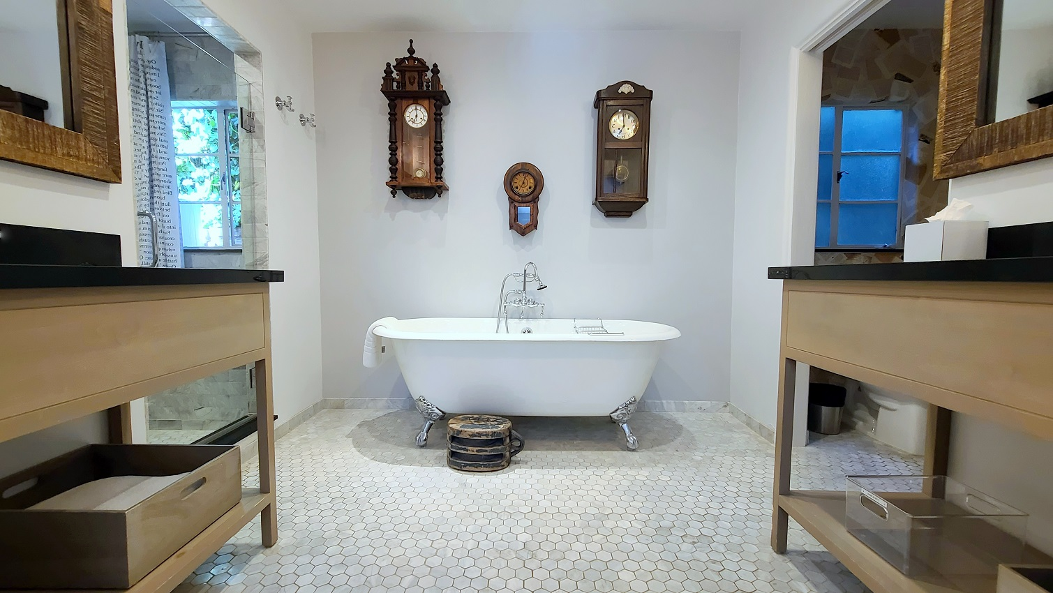 free standing tub with three clocks over it